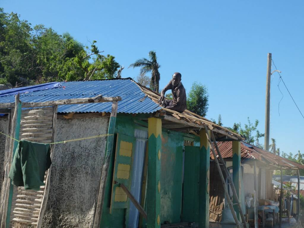 Ein Einwohner repariert das Dach seines Hauses.