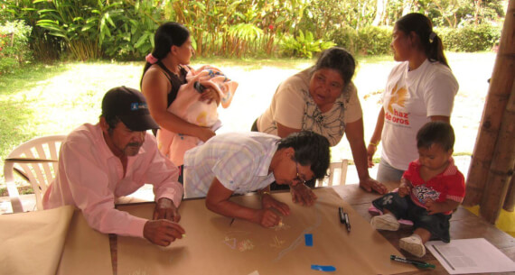 Männer und Frauen einer Gemeinde arbeiten an einem Tisch, eine Teilnehmende trägt ein Baby in einem Tuch