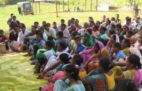 Informationsveranstaltung von Adivasi, die draussen im Grünen am Boden sitzen