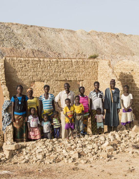 Grossfamilie vor Haus, das die Mine zerstört hat. Foto: Fastenopfer/Meinrad Schade