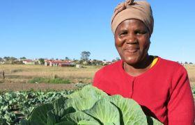 Eine Frau aus dem Projekt des Rural Women Assembly zeigt stolz ihre Ernte