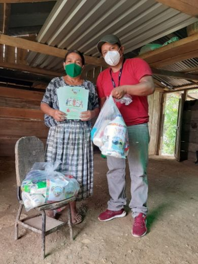 Zwei Mitarbeitende der Organisation Tzuul Taq'a verteilten gleichzeitig Informationen zu Covid und dringend benötigte Nahrungsmittel.