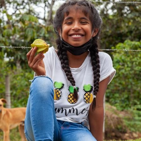 Kolumbien ATUCSARA, Mädchen zeigt Frucht