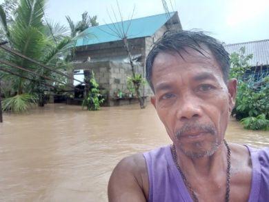Mitarbeiter Marcelino von TCD Infanta zeigt, wie hoch das Wasser in seinem Dorf steht.