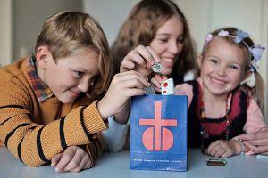 Kinder füllen ein Fastensaecklein für eine Fastenaktion in einer Pfarrei während der Fastenzeit. Bild von Romana Büchel.